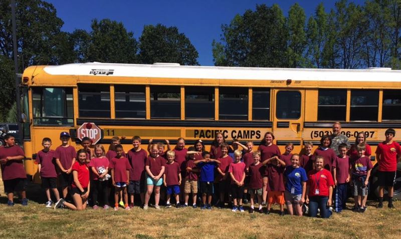 PHOTO COURTESY OF APRIL BURBANK - Students at Pacific Camps St. Helens stand in front of a newly acquired bus that was purchased with donations from numerous community members collected in July. The summer camp program lost its bus July 8 in an arson fire.