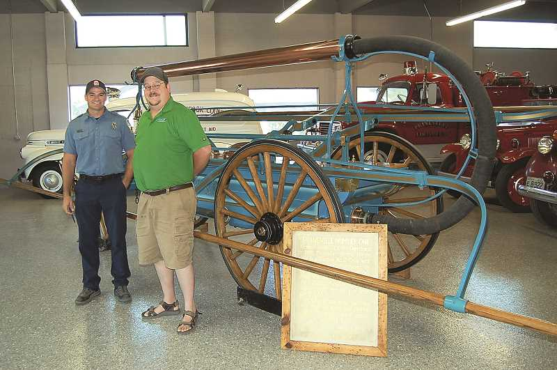 PHOTO BY RAMONA MCCALLISTER  - Russ Deboodt, left, and Ray Austin stand by Prineville's second fire engine, which was restored in 1978. The PVFC helps maintain the local fire department's impressive display of historic equipment.