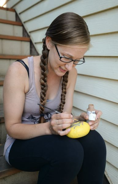OUTLOOK PHOTO: JOSH KULLA - Gresham resident Sarah Bourgeois puts the finishing touches on yet another painted rock that she will sell or trade. Thousands of similar artistic rocks have been spread across East Multnomah County by similarly-minded artists.