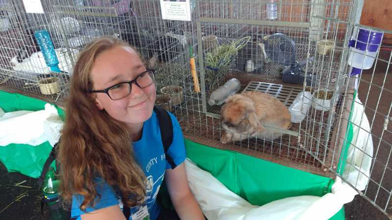 NEWS-TIMES PHOTO: STEPHANIE HAUGEN  - Anna Wagnon, 15, of Hillsboro, interacted with the public during opening day of the fair, talking with passersby about her rabbit.