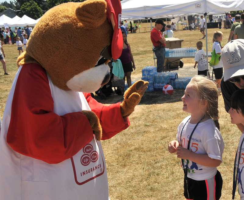 SPOKESMAN PHOTO: VERN UYETAKE  - Brianna Hartzell visits with the State Farm Bear at Saturdays event.