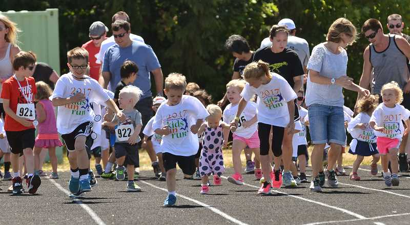 SPOKESMAN PHOTO: VERN UYETAKE  - Preschoolers make a mad dash as they race to the finish line.
