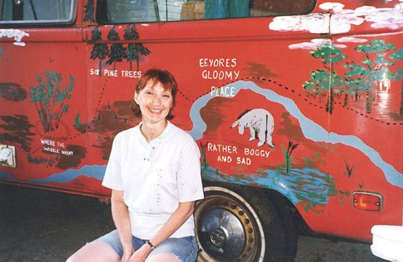 SUBMITTED PHOTO - Shawn Van Doren, one of the artists showing her work in the North Clackamas Arts Guild show, poses with her paintings on the side of a 'Pooh van.'