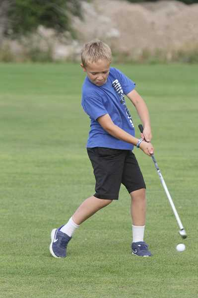 WILL DENNER/MADRAS PIONEER - Jake Gassner, 8, takes a swing at the ball with an iron on the seventh hole at Desert Peaks Golf Club July 25.