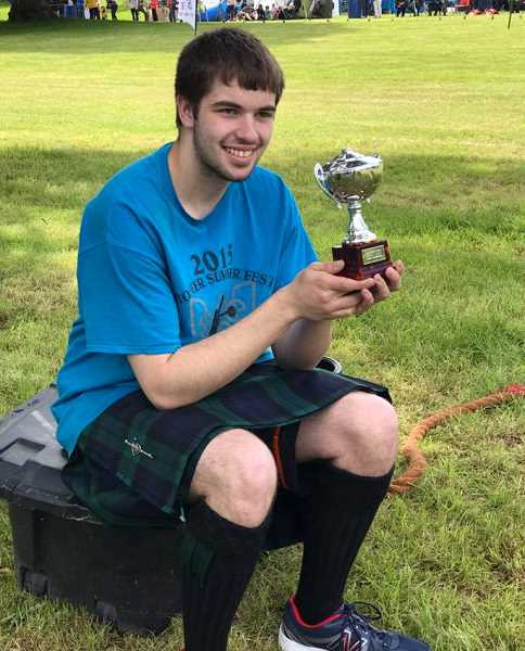PHOTO COURTESY OF FRANKLIN CARROLL - Isaac Moore displays the trophy he won for taking first in the junior division of the Strathmore Highland Games, which take place annually in County Dublin, Scotland. Moore was visiting Scotland for his senior trip after graduating from Crook County High School earlier this summer.
