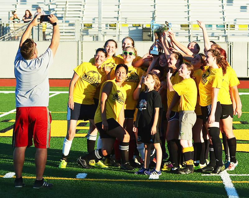 SPOTLIGHT PHOTO: JAKE MCNEAL - Last year's St. Helens girls' soccer alumni celebrate their 2-1 win with the Maye-Strawn Trophy, which honors the memory of Elizabeth Maye and Amanda Maye-Strawn who passed away in a car accident in 2014 as Lions coach Simon Date, left, readies the photo.