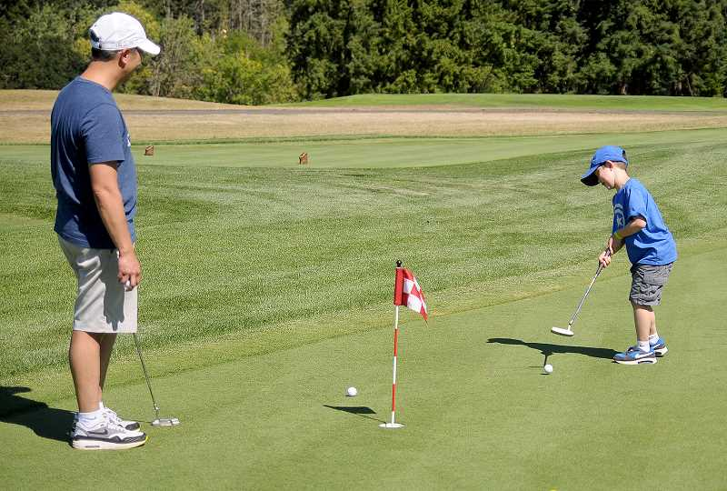 SETH GORDON - Newberg resident Jon Fong and his 5-year-old son, Coby, enjoy the new nine-hole natural grass putting course at Chehalem Glenn Golf Course.