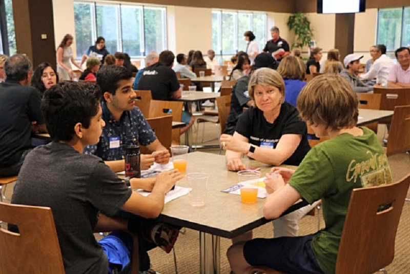 SUBMITTED PHOTO: COURTESY OF PACSTAR - Mary Kay Petersen, information technology director of Mentor Graphics, was one of the speakers at the PDX Cyber Camp. Here, Petersen chats with a few students.