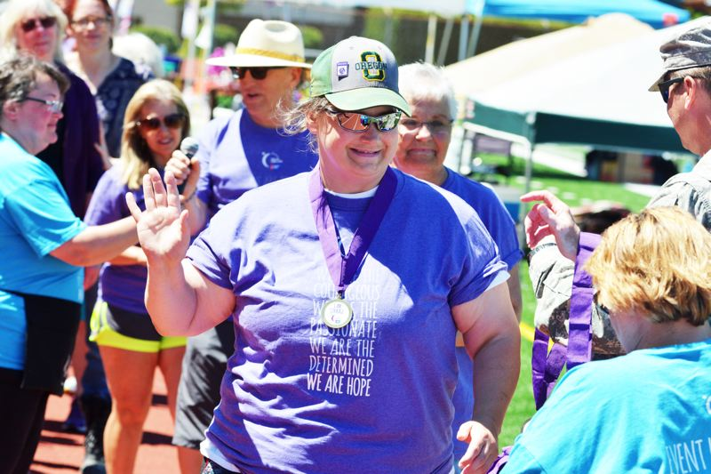 SPOTLIGHT PHOTO: JAKE MCNEAL - Survivor Dawn Getzlaff, a cancer survivor and a caretaker for Margaret Brady, receives a Relay for Life medal for her bravery.