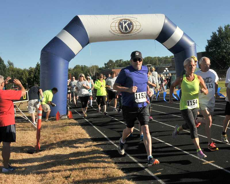 SPOKESMAN PHOTO: VERN UYETAKE - Runners head out from the start of the Wilsonville Kiawanis 5k race Saturday morning.