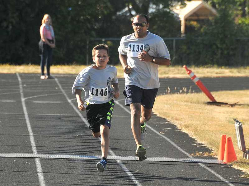 SPOKESMAN PHOTO: VERN UYETAKE - Ten-year-old Sam Soto makes a strong dash for the finish in the 5k race.