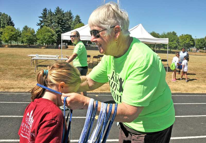 SPOKESMAN PHOTO: VERN UYETAKE - Volunteer Lavon Ostrick awards kids with their medals at the finish line.