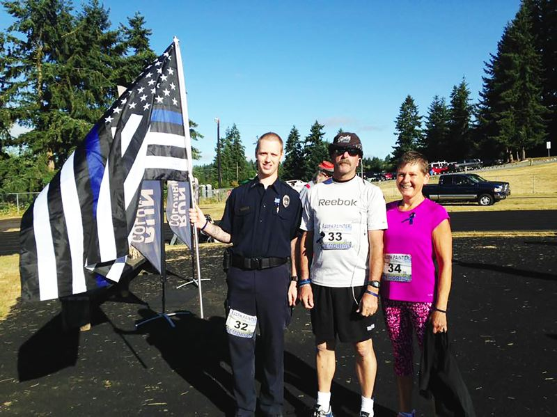 PHOTO CREDIT: RALPH PAINTER MEMORIAL 10K, 5K AND KIDS RACE - Brandon Holt, 24, of the Warrenton Fire Department (32), with Bruce Holt, 59 (33) and Dana Holt, 57 (34) carries a Thin Blue Line Flag in honor of Rainier police chief Ralph Painter, who was killed in performance of his duties in 2011.
