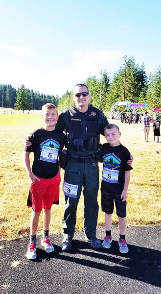 PHOTO CREDIT: RALPH PAINTER MEMORIAL 10K, 5K AND KIDS RACE - From left, Kalama, Wash.'s Ethan Brightbill, 11 (6), Cowlitz County sergeant Troy Brightbill, 42 (9) and Benji Brightbill, 8 (5) pose for a photo.