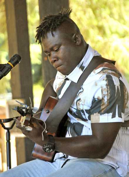 TIDINGS PHOTOS: VERN UYETAKE - Okaidja Afroso uses songs to bring stories to life from his native Ghana at last week's Willamette Park Kids Program series.