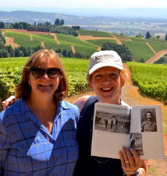SUBMITTED PHOTO:  - Barb Randall, left, poses with her friend, Page Knudsen Cowles in the Knudsen Vineyards in Dundee. Page is holding a copy of Randalls book Willamette Valley Wineries opened to a picture of Page and her brothers walking up the same vineyard in which she and Randall are standing.