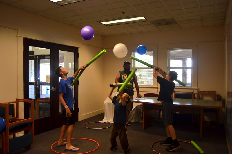 SPOTLIGHT PHOTO: NICOLE THILL - From left to right, Andrew Pletsch, 13, Jude Swift, 6, and Quinn Swift, 9, participate in the 'Rey's Lightsaber Challenge,' where participants were asked to keep a balloon afloat using lightsabers made of green foam pool toys for at least 15 seconds. All three boys took the challenge seriously and pushed themselves to keep their balloons in the air for 30 seconds.