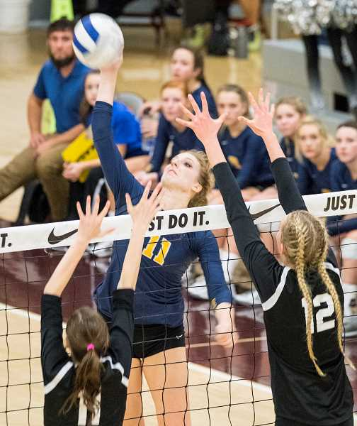 LON AUSTIN/CENTRAL OREGONIAN - Jennifer Roth hits a shot past a double block during the 2016 volleyball state championship game. Roth will play her college volleyball at MidAmerica Nazarene University in Olathe, Kansas.