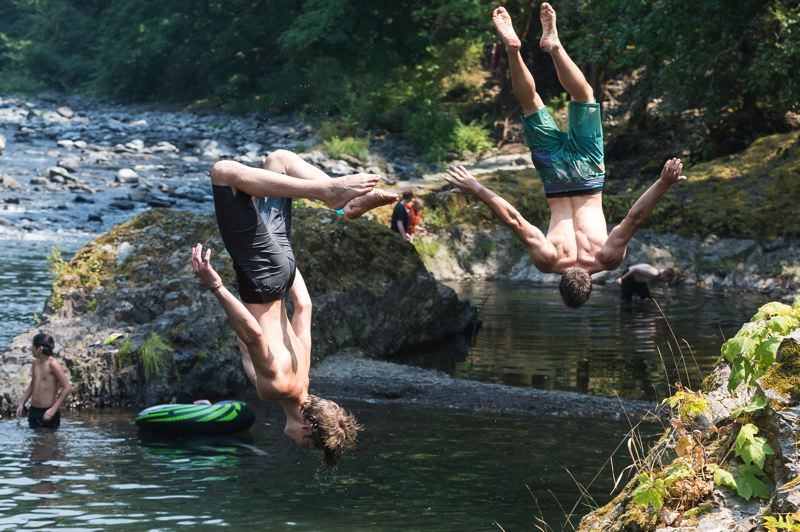 NEWS-TIMES PHOTO: CHRISTOPHER OERTELL - Keenan Smith, 15, and his brother Elijah, 17, both from Portland, jump off a rock into the Wilson River near the Smith Homestead Day Use Area.
