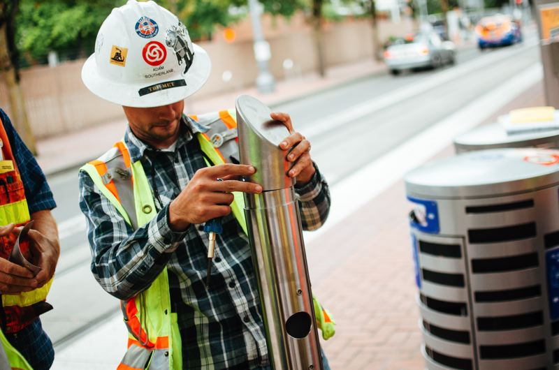 TRIMET PHOTO - A TriMet worker inspects a HOP pass machine