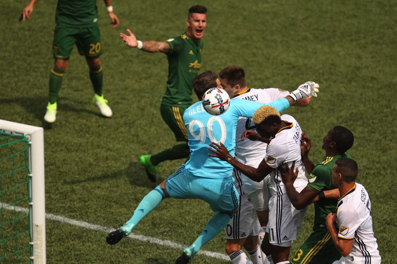TRIBUNE PHOTO: JAIME VALDEZ - Los Angeles Galaxy forward Gyasi Zerdes (11) leads in with his shoulder and collides with Portland Timbers goalkeeper Jake Gleeson during the first half Sunday at Providence Park.