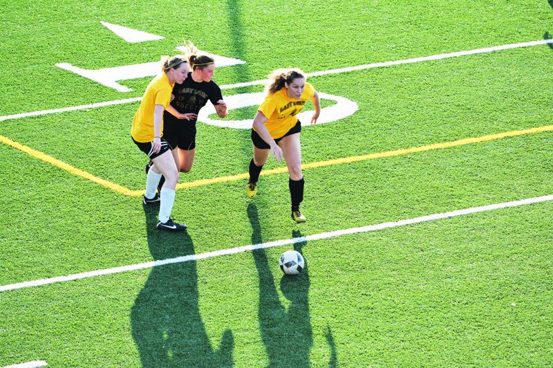 SPOTLIGHT PHOTO: JAKE MCNEAL - Dana Sukau and Regan Duarte (Alumni, in yellow) race Kaela Lee (of the Preps, in black) for control of a pass.