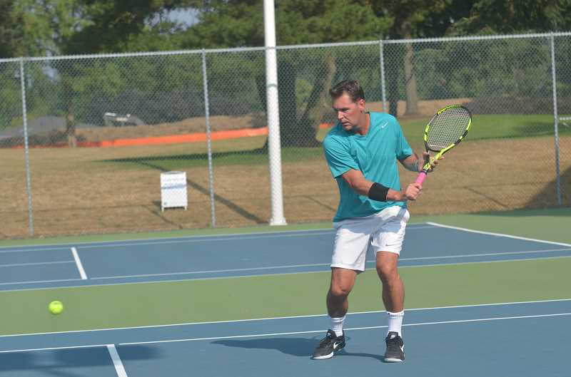 SPOKESMAN PHOTO: COREY BUCHANAN - Former Charbonneau Tennis Club professional Brian Joelson eyes an approach shot near the net in the men's doubles exhibition at Charbonneau Tennis Club Sunday, Aug. 6.