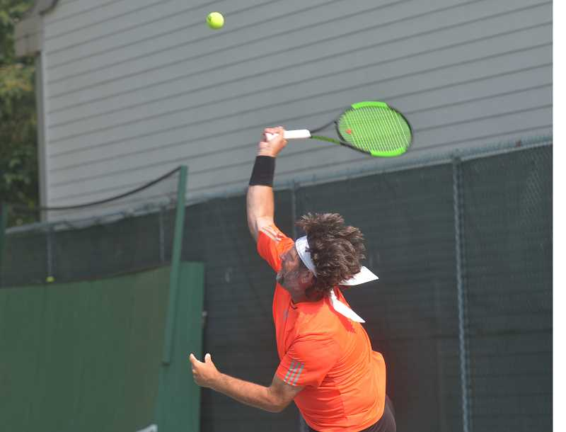 SPOKESMAN PHOTO: COREY BUCHANAN - Charbonneau Tennis Club professional Craig Koessler smacks a serve during the men's doubles exhibition.