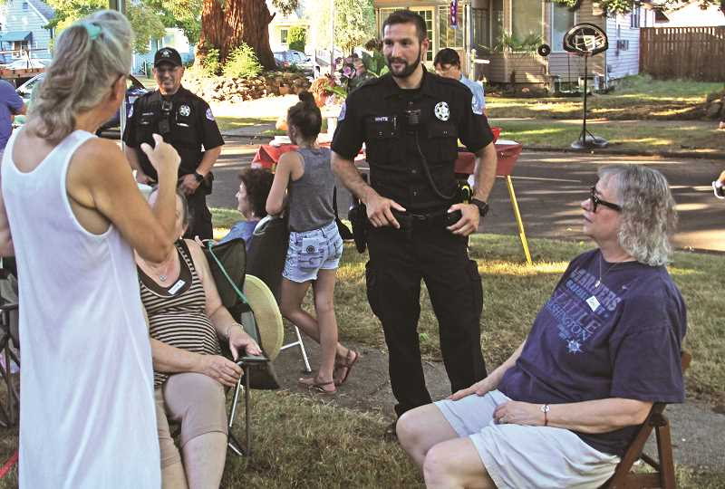 INDEPENDENT PHOTO: JULIA COMNES - Officer Travis White of the Woodburn Police Department chats with residents attending the National Night Out block party on Grant Street. The event aims to promote police-community partnerships.
