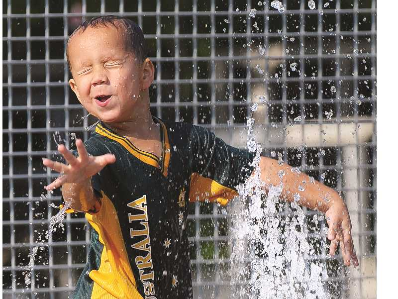 GARY ALLEN - Four-year-old Dario Calderon enjoys the cool water provided by the splash pad at Rotary Centennial Park last week.
