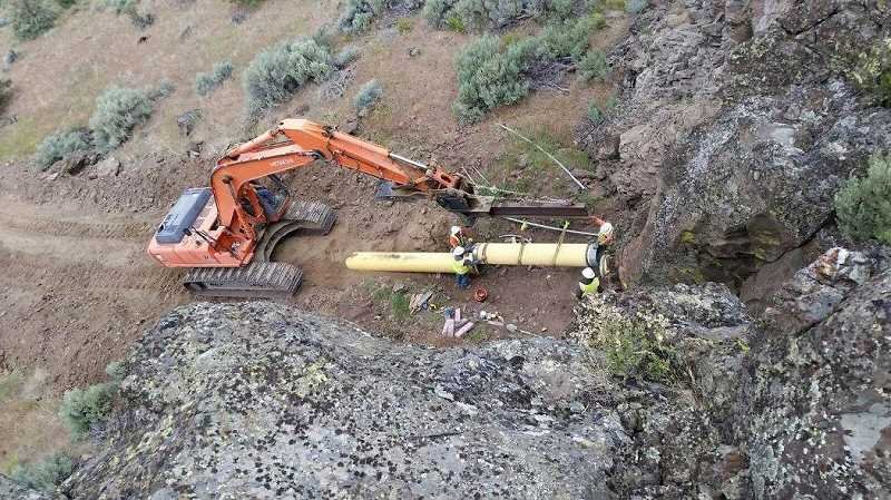 PHOTO COURTESY OF DVWD - Workers wrap up the steep hill portion of Deschutes Valley Water District's new 24-inch pipe in 2016.