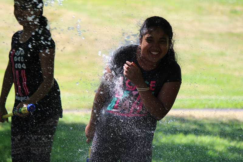 SPOKESMAN PHOTO: SAM STITES - Vindhya Adamala gets drenched by a blast of water during a water fight in Murase Plaza park.