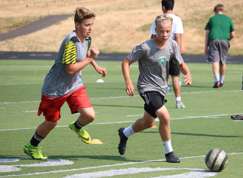 REVIEW/NEWS PHOTO:  - Putnam's Jack Mathews (left) closes on Roman Quick during Wednesday morning's boys' soccer workout at Putnam High School.