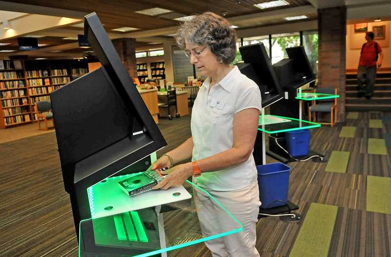 REVIEW PHOTO: VERN UYETAKE - Librarian Lisa Buchholz uses one of the new automated checkout stations in the front lobby of the Lake Oswego Public Library. The stations use RFID sensors to scan entire stacks of books at one time.