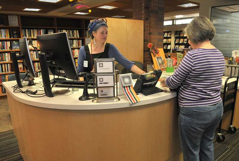 REVIEW PHOTO: VERN UYETAKE - Kiira Taylor helps visitors at the library's new adult services desk.