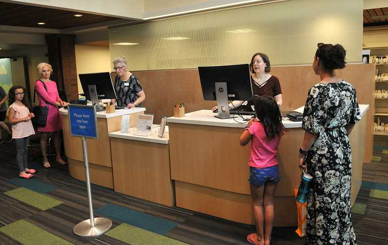 REVIEW PHOTO: VERN UYETAKE - Lake Oswego residents check out materials from the library's new front counter.