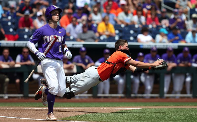 SCOTT CASSIDY: FOR THE TIMES - Oregon State University catcher Adley Rutschman, a Sherwood graduate, makes a diving catch during play at the 2017 College Baseball World Series.