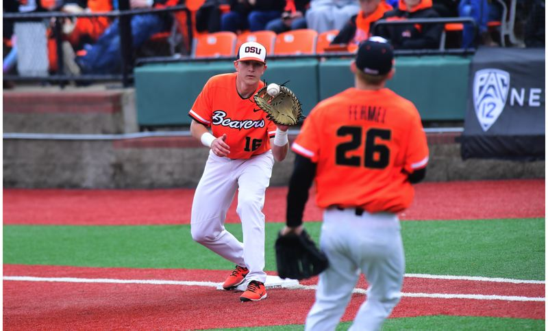 DAVE NISHITANI: OREGON STATE UNIVERSITY - Sherwood High School graduate Zak Taylor (left) makes a catch at first base during play this past season for the Oregon State University baseball team. Taylor helped the Beavers reach the 2017 College Baseball World Series.