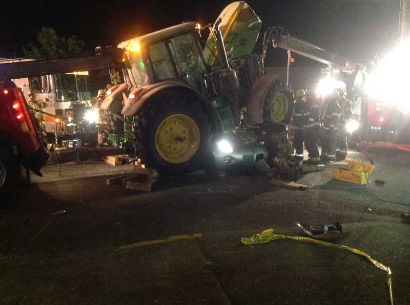 COURTESY PHOTO - Firefighters needed to call in Hillsboro towing to help lift the tractor off the sportscar.