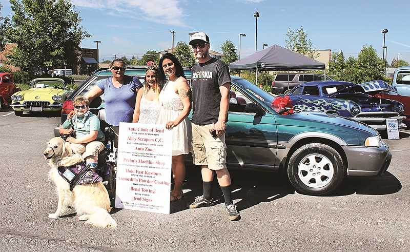 HOLLY SCHOLZ/CENTRAL OREGONIAN   - Left to right: Stryder Doescher, his service dog, Keebler, Angela Doescher, Kasiah Childers, Auto Clinic of Bend owner Julieann Wilson, and Alley Scrapers Car Club member Mike McGovern.