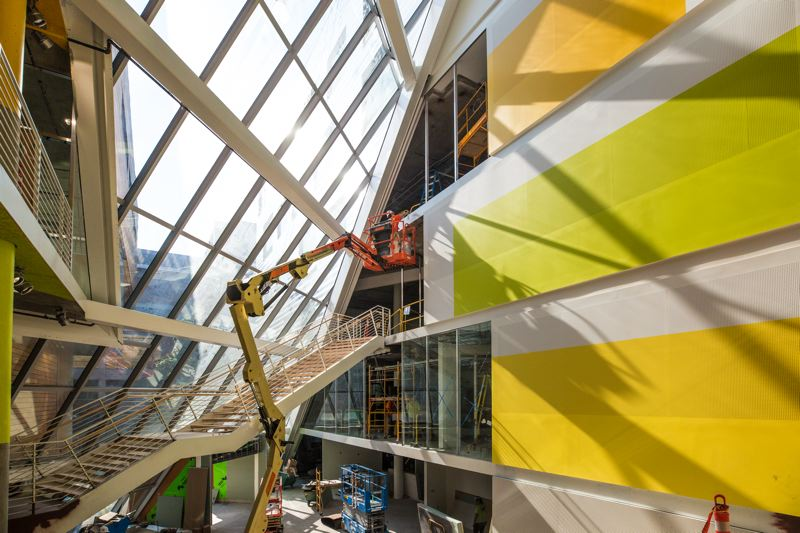 PAMPLIN MEDIA GROUP: JONATHAN HOUSE - A subcontractor paints the window frame white on the new atrium at SW 6th Avenue near Montgomery St downtown.