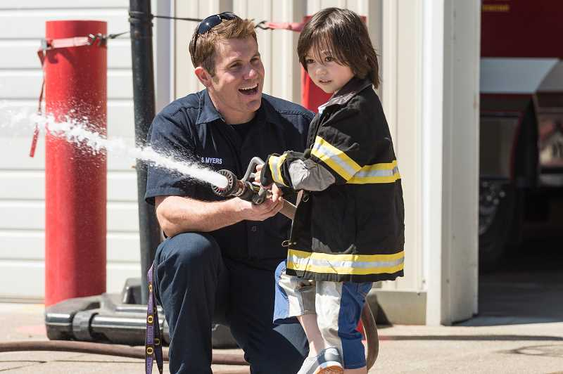 HILLSBORO TRIBUNE PHOTO: CHRISTOPHER OERTELL - Tualatin Valley Fire and Rescue Public Information Officer Stefan Meyers helps Kazuma Eisenberg, 4, from North Plains, with the fire hose at the TVF&R open house on Aug. 5 at Station 19.