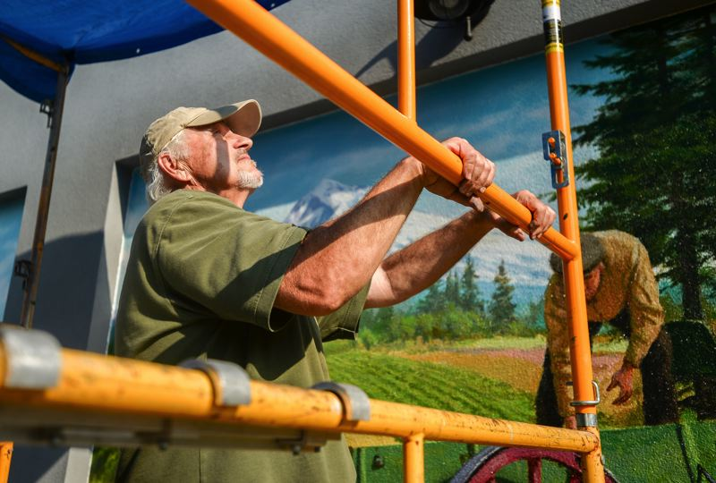 OUTLOOK PHOTO: JOSH KULLA - Artist Don Gray examines his work Wednesday, as he completed a pair of scenes celebrating Gresham's history of berry farming and picking. The new mural can be seen on the south wall of Jazzy Bagels facing Powell Boulevard.