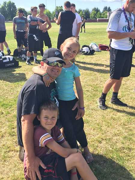 COURTESY PHOTO - New Century head football coach Sean McMenomy with his son Quinlan and daughter Reece.