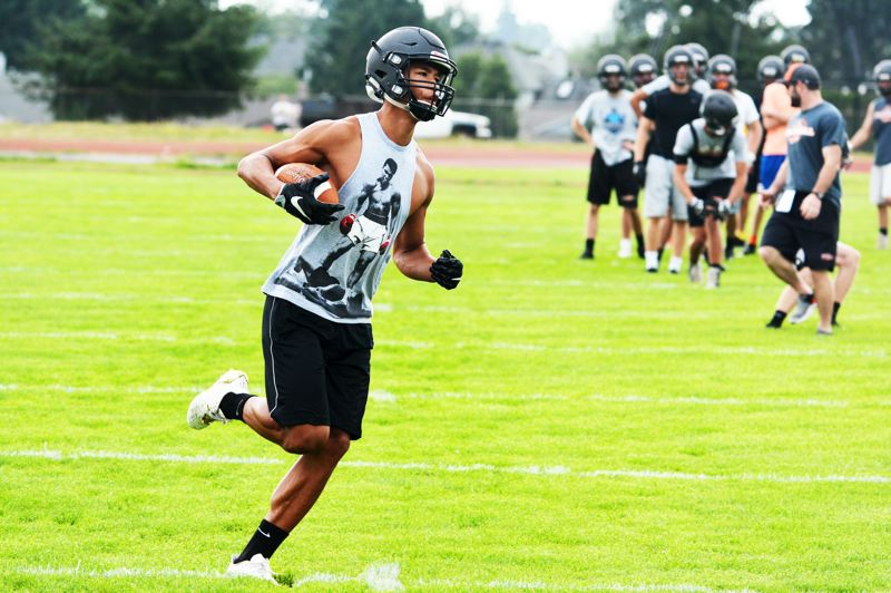 SPOTLIGHT PHOTO: JAKE MCNEAL - Indians senior wide receiver Tevin Jeannis pulls in a catch during a receiver drill.