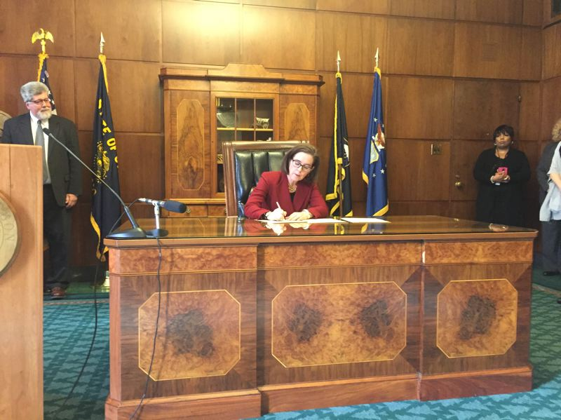 PARIS ACHEN/CAPITAL BUREAU - Gov. Kate Brown signs an executive order Feb. 2, 2017, inside her ceremonial office at the Oregon State Capitol in Salem.