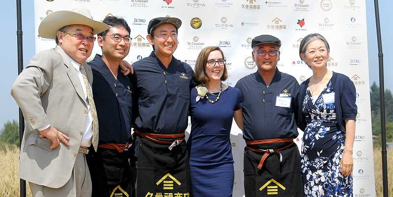 AARON KNAPP - Gov. Kate Brown poses with members of the Kuze family, who own a Japanese company called St. Cousair, during a grand opening ceremony for their new facility Aug 9. Having recently acquired Newberg food processing company Berry Noir, St. Cousair Oregon Orchards won a $100,000 state grant that will allow them to add 18 new jobs to the facility on Highway 219 south of the city.