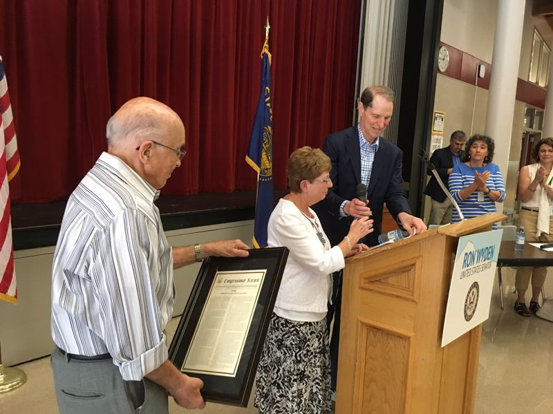 PAMPLIN MEDIA GROUP: PETER WONG - Holocaust survivors Les and Eva Aigner of Portland, left, receive a framed statement from the Congressional Record and a U.S. flag flown over the Capitol in Washington, D.C., from U.S. Sen. Ron Wyden, D-Ore., at a town hall meeting Aug. 9 at Hazelbrook Middle School in Tualatin. Among those applauding is Jill Zurschmeide, Tigard-Tualatin School Board chairwoman.