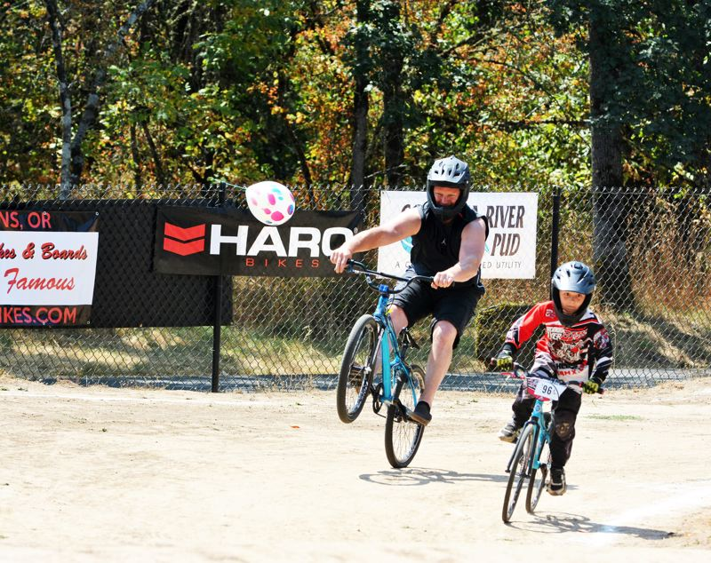 SPOTLIGHT PHOTO: JAKE MCNEAL - Eric Filley, owner of Portland's Halo Electric, LLC, left, enjoys a wheelie with Titus Griffin, 8, of St. Helens.
