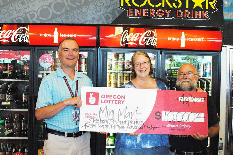 NEWS-TIMES PHOTO: STEPHANIE HAUGEN - (Left to right) Oregon Lottery field sales representative Jerry Strauss, Sherri Musselwhite, Jimmie Musselwhite and Oregon Lottery representative Patrick Johnson were all happy about the $10,000 bonus the Mini Mart owners received.